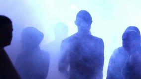 Gente joven que baila en una porción del club nocturno de humo almacen de metraje de vídeo