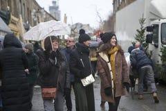 Gente joven que camina abajo de la calle, hablando en el teléfono en la lluvia Imágenes de archivo libres de regalías