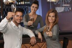 Gente joven que celebra con champán en barra Imagen de archivo libre de regalías