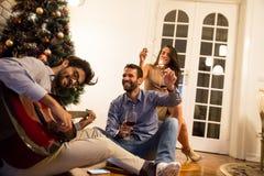 Gente joven que celebra la Navidad y el Año Nuevo por el abeto en h Foto de archivo
