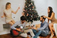 Gente joven que celebra la Navidad y el Año Nuevo por el abeto en h Imágenes de archivo libres de regalías