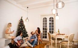 Gente joven que celebra la Navidad y el Año Nuevo por el abeto en h Fotos de archivo