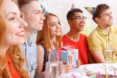 Gente joven que celebra un cumpleaños que se sienta en Foto de archivo libre de regalías