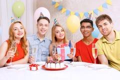 Gente joven que celebra un cumpleaños que se sienta en Fotos de archivo libres de regalías
