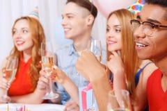 Gente joven que celebra un cumpleaños que se sienta en Fotografía de archivo