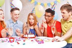 Gente joven que celebra un cumpleaños que se sienta en Fotografía de archivo libre de regalías