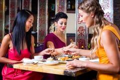Gente joven que come el sushi en restaurante Imágenes de archivo libres de regalías