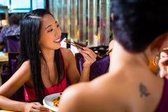 Gente joven que come en el restaurante de Asia Imagen de archivo libre de regalías