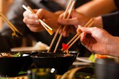 Gente joven que come en restaurante tailandés foto de archivo