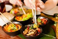 Gente joven que come en restaurante tailandés imagenes de archivo
