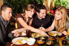 Gente joven que come en restaurante tailandés imagen de archivo
