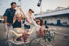 Gente joven que compite con con el carro de la compra y que celebra con el conf imagen de archivo