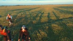 Gente joven que completa un ciclo en las bicicletas a través de campo verde y amarillo del prado del verano almacen de video