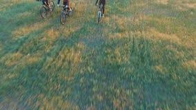 Gente joven que completa un ciclo en las bicicletas a través de campo verde y amarillo del prado del verano almacen de metraje de vídeo