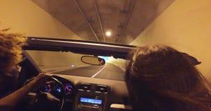 Gente joven que conduce a través del túnel en coche convertible almacen de metraje de vídeo