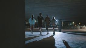Gente joven que corre en la playa por mañana almacen de video