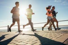 Gente joven que corre a lo largo de la playa imagenes de archivo