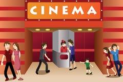Gente joven que cuelga hacia fuera fuera de un cine Imágenes de archivo libres de regalías