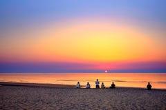 Gente joven que cuenta con la salida del sol en la playa y toma imágenes con su teléfono elegante Fotografía de archivo