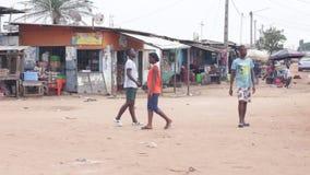 Gente joven que da un paseo abajo de la calle que separa el pueblo almacen de video