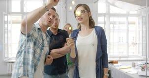 Gente joven que dibuja en el tablero de cristal metrajes