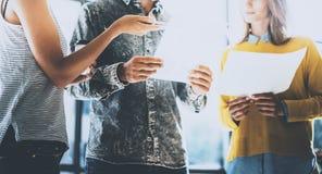 Gente joven que discute ideas del negocio en una oficina Sirva sostener el papel sus manos y hablar con una mujer horizontal Foto de archivo libre de regalías