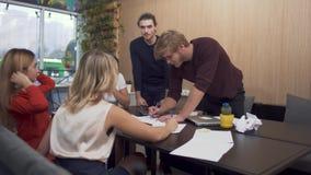 Gente joven que discute intenso planes en la tabla de la sala de reunión Planes empresariales diarios del análisis almacen de metraje de vídeo