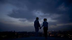 Gente joven que disfruta de la tarde romántica en el tejado, ciudad iluminada en la noche foto de archivo