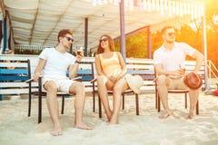 Gente joven que disfruta de las vacaciones de verano que toman el sol la consumición en la barra de la playa Imagenes de archivo