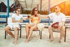 Gente joven que disfruta de las vacaciones de verano que toman el sol la consumición en la barra de la playa Foto de archivo