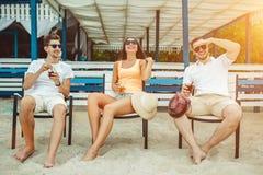 Gente joven que disfruta de las vacaciones de verano que toman el sol la consumición en la barra de la playa Fotos de archivo