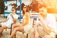 Gente joven que disfruta de las vacaciones de verano que toman el sol la consumición en la barra de la playa Foto de archivo libre de regalías