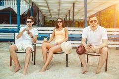 Gente joven que disfruta de las vacaciones de verano que toman el sol la consumición en la barra de la playa Fotos de archivo libres de regalías