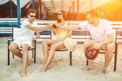 Gente joven que disfruta de las vacaciones de verano que toman el sol la consumición en la barra de la playa Imágenes de archivo libres de regalías