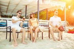 Gente joven que disfruta de las vacaciones de verano que toman el sol la consumición en la barra de la playa Imagen de archivo libre de regalías