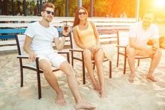 Gente joven que disfruta de las vacaciones de verano que toman el sol la consumición en la barra de la playa Fotografía de archivo