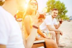 Gente joven que disfruta de las vacaciones de verano que toman el sol la consumición en la barra de la playa Fotografía de archivo libre de regalías