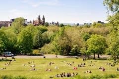 Gente joven que disfruta de un día soleado caliente en el parque de Kelvingrove de Glasgow foto de archivo libre de regalías