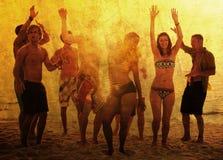 Gente joven que disfruta de un partido de la playa del verano imagenes de archivo