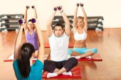 Gente joven que ejercita con pesas de gimnasia Foto de archivo