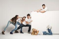 Gente joven que empuja a la tarjeta blanca Foto de archivo libre de regalías