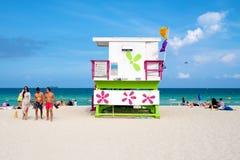 Gente joven que goza de la playa al lado de una remolque colorida del salvavidas Imágenes de archivo libres de regalías