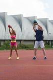 Gente joven que hace el ejercicio de Bell de la caldera al aire libre Imagenes de archivo