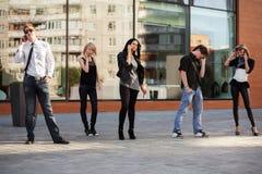 Gente joven que invita a los teléfonos celulares Fotografía de archivo