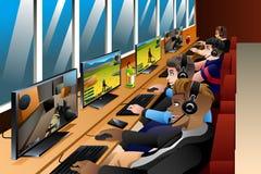 Gente joven que juega a juegos en un café de Internet Imágenes de archivo libres de regalías