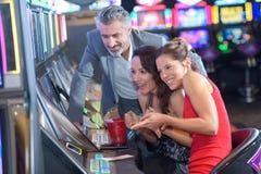 Gente joven que juega las máquinas tragaperras en casino imagenes de archivo