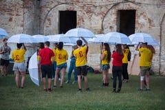 Gente joven que juega a un juego con los paraguas blancos Fotos de archivo