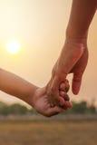 gente joven que lleva a cabo las manos en puesta del sol Imagenes de archivo