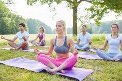 Gente joven que medita en clase de la yoga Foto de archivo libre de regalías