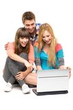 Gente joven que mira la computadora portátil Imagenes de archivo